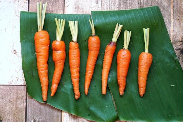Свежая органическая морковь на банановом листе и деревянном фоне