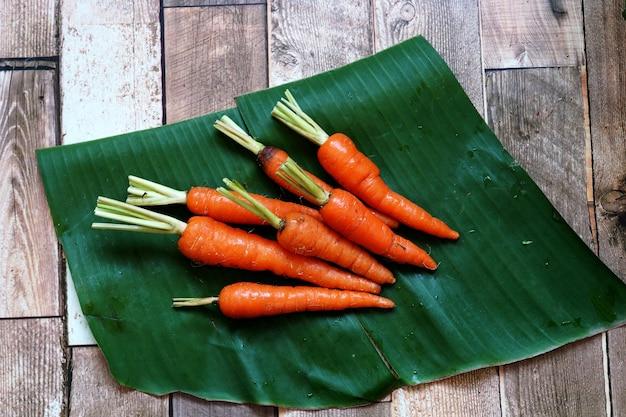 Свежая органическая морковь на зеленом банановом листе и деревянном фоне