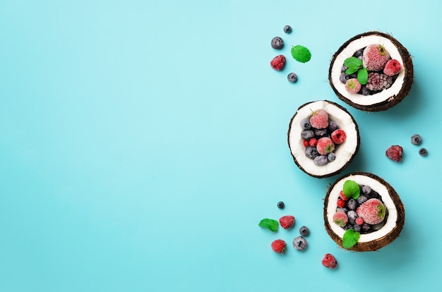 Fresh organic berries, mint leaves inside ripe coconuts. top view. pop art design, creative summer concept. half of coconut in minimal flat lay style.