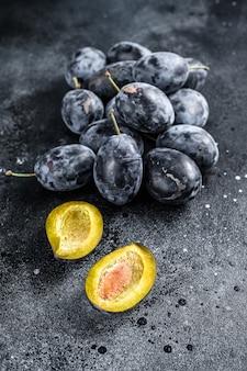 Fresh organic bio plums. black background. top view.