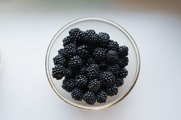 Свежие органические ягоды ежевики в прозрачной тарелке на столе