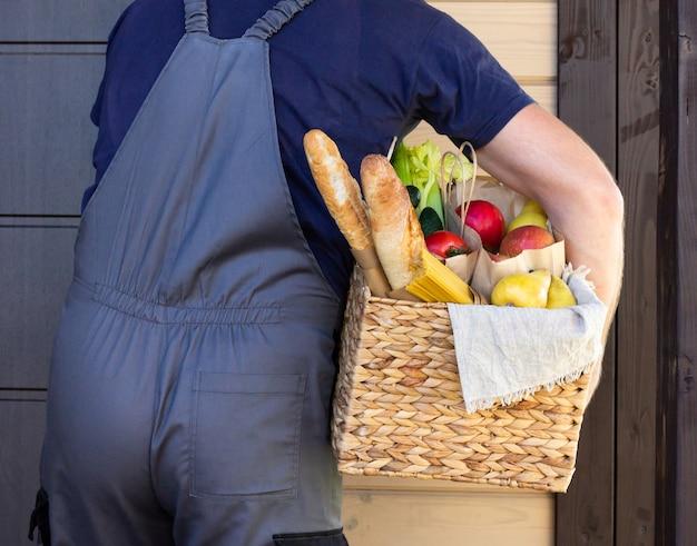 自転車の宅配便の手にある籐のバスケットに入った焼きたての有機パン、野菜、野菜、果物、シリアル、パスタ。バイクの環境にやさしい配達またはエコロジカルファームフードコンセプトの寄付。