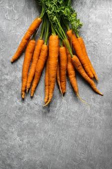 Mazzo organico fresco di carote su una vista aerea superiore della cucina grigia