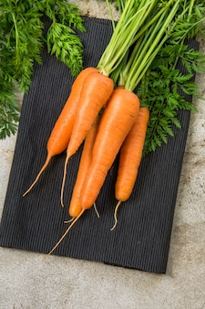 Fresh organic carrots with green tops on rustic table, closeup. top view.