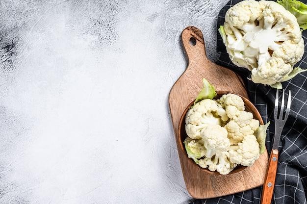 Fresh organic cauliflower cut into small pieces in wooden bowl