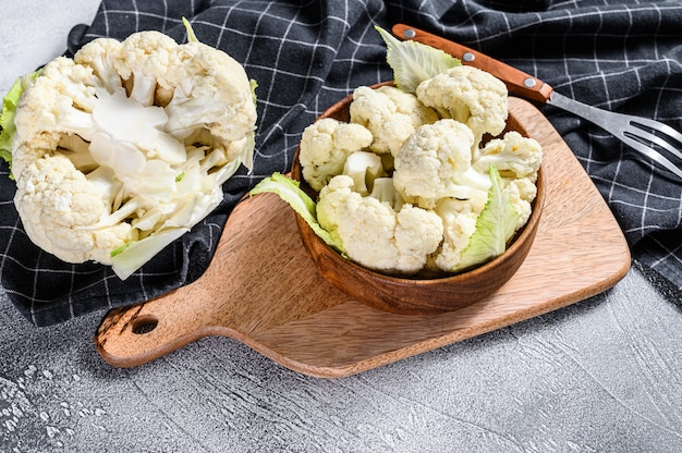 Fresh organic cauliflower cut into small pieces in wooden bowl