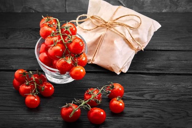 Свежие органические помидоры черри на темном фоне, доставка еды. скопируйте пространство.