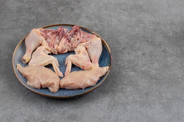 회색 테이블 위에 파란색 접시에 신선한 유기농 닭고기.