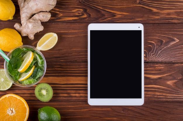 新鮮な有機柑橘系の果物とデトックスと木製の背景にタブレット。健康食品と健康的な生活の概念。上面図