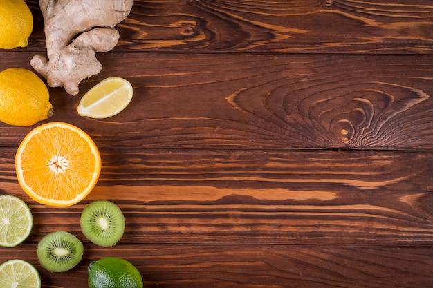 新鮮な有機柑橘系の果物と木製の背景。健康食品と健康的な生活の概念。上面図
