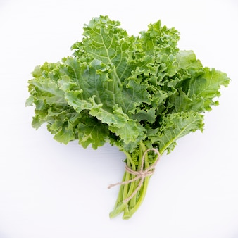 Fresh organic curly kale leaves flat lay on a wooden table with copy space.