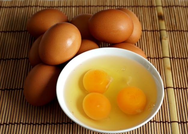 대나무 매트에 있는 그릇에 신선한 유기농 계란