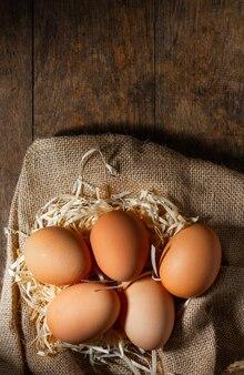 나무 테이블에 마른 잔디와 삼 베에 신선한 유기농 계란.