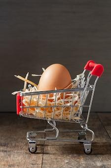 식료품 쇼핑 카트에 마른 풀이 있는 신선한 유기농 계란.