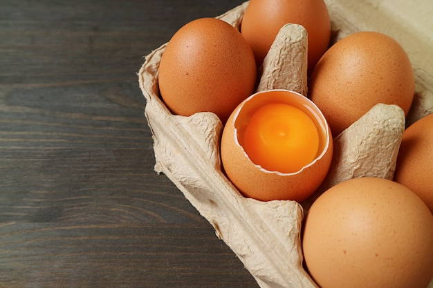 Fresh organic eggs with one of opened shell in a carton box