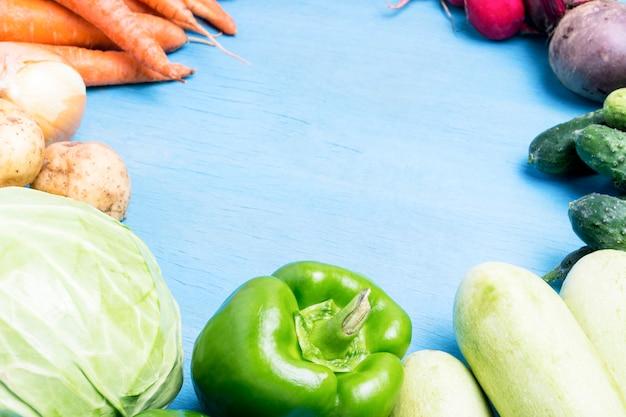 Свежие органические овощи фермы, здравоохранение, на синем фоне деревянные. уборка урожая. стиль кантри. форма круга. концепция фермы ярмарка. плоская планировка, вид сверху