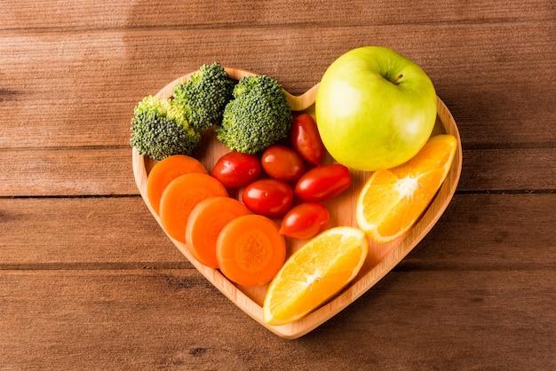 나무 테이블에 하트 플레이트 나무에 신선한 유기농 과일과 야채