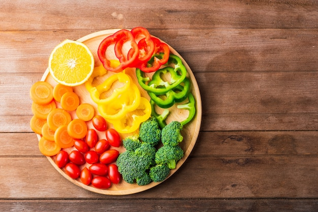 Свежие органические фрукты и овощи в деревянной тарелке