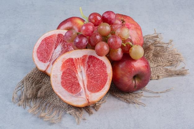 Frutta biologica fresca. mela, uva e mandarini su sfondo grigio.