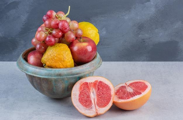 Fresh organic fruits in bowl on grey background.