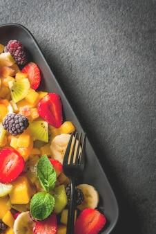 Свежие органические фрукты манго, персик, яблоко, банан, киви, клубника, ежевика на черной керамической тарелке