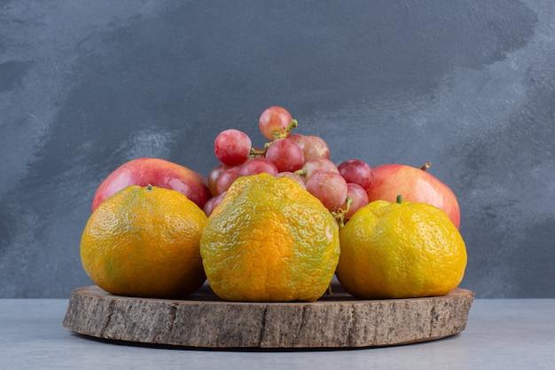 나무 보드에 신선한 유기농 과일입니다. 귤, 붉은 포도, 사과.