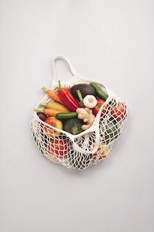 Fresh organic fruits and vegetables in mesh textile bag