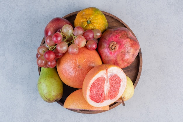 Fresh organic fruits in wooden bowl on grey background.