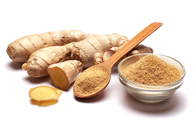 Fresh organic ginger and bowl of grinded spice isolated on white surface