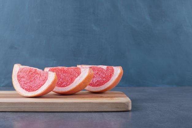 Fette di pompelmo biologico fresco su tavola di legno.