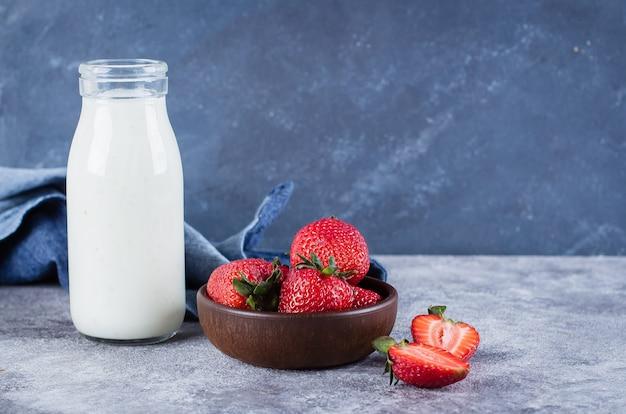 Fresh organic greek yogurt or milk with strawberries on gray concrete table background.
