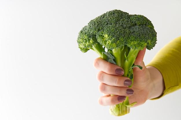 女性の手で新鮮な有機グリーンブロッコリー、コンセプト健康食品。分離されたブロッコリーを持っている女性の手。
