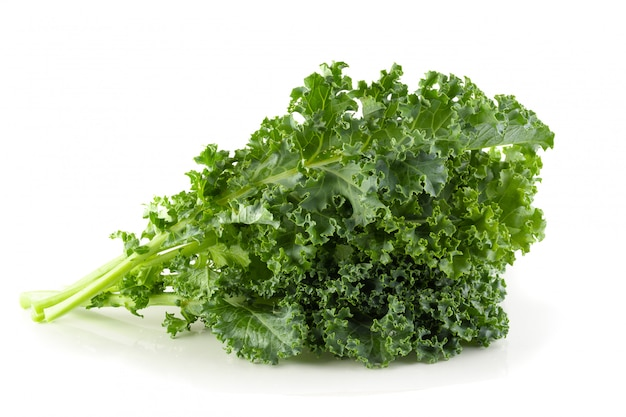Fresh organic green kale leaves isolated over white background