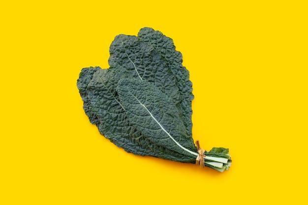 Свежие органические зеленые листья капусты на желтом.