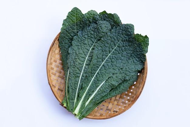 Fresh organic green kale leaves in wooden bamboo threshing basket on white