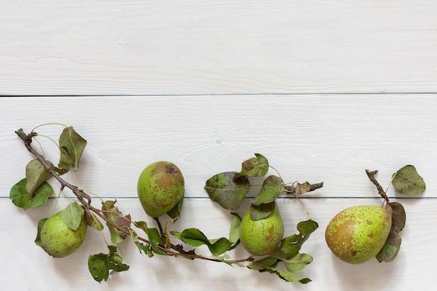 자연 흰색 나무 벽에 잎을 가진 신선한 유기농 녹색 배