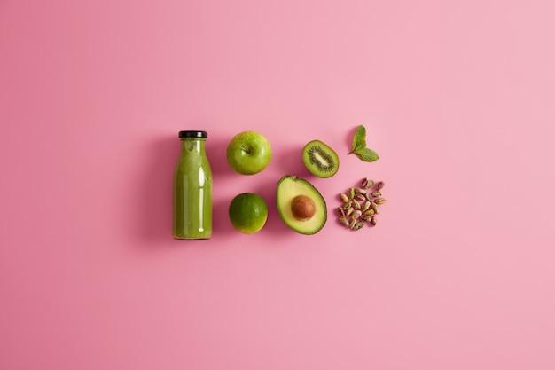 Свежий органический зеленый коктейль и ингредиенты яблочный лайм, половина авокадо, фисташки и мяты на розовом фоне. безалкогольный питательный вегетарианский напиток. натуральное детокс-питание. концепция диеты