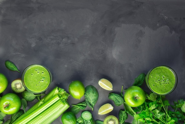 Fresh organic green smoothie with ingredients on gray concrete