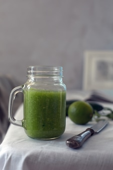 Fresh organic green smoothie with spinach, cucumber on a white tableware