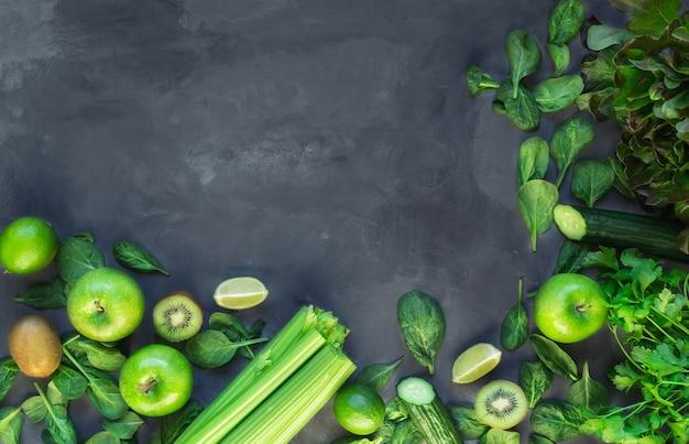 新鮮な有機野菜や果物。灰色のコンクリートの背景に緑のスムージーの成分。上面図。スペース領域をコピーします。 Premium写真