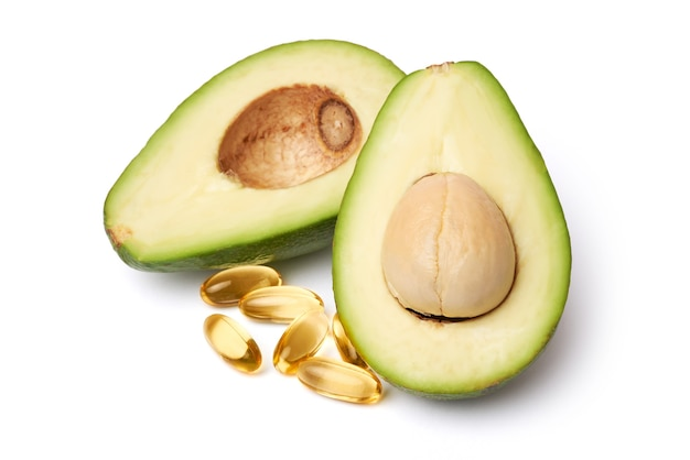 Fresh organic halved avocado and capsules with omega-3 isolated