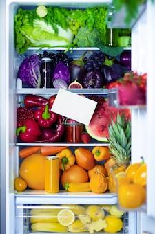 新鮮な有機健康生抗酸化剤バイオレット、赤、緑、オレンジ、黄色の食品、野菜、果物、ジュース、菜食主義者の菜食主義者は、テキスト用のスペースを持つビタミンの冷蔵庫を完全に開きました。健康的な食事。