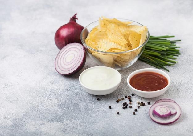 軽いキッチンテーブル背景にサワークリームと赤玉ねぎとガラスのボウルで新鮮な有機自家製ポテトチップスチップ。