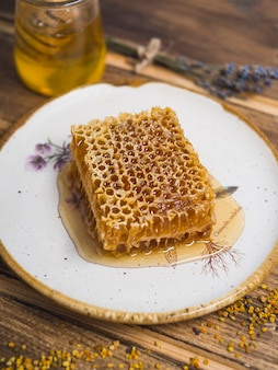 Fresh organic honeycomb on plate with bee pollens over table