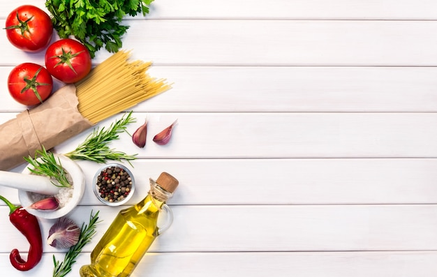 Fresh organic ingredients, pasta spaghetti of italian recipes. healthy food concept on white wooden table background. top view, copy space.