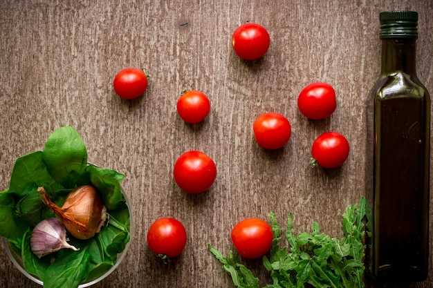 Fresh organic ingredients for salad making: spinach, tomatoes, sprouts, basil, olive oil on rustic background, top view. flat lay with place for text. vegan and healthy food concept