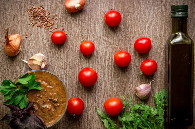 Fresh organic ingredients for sauce making: spinach, tomatoes, sprouts, basil, olive oil on rustic background, top view. flat lay with place for text. vegan and healthy food concept