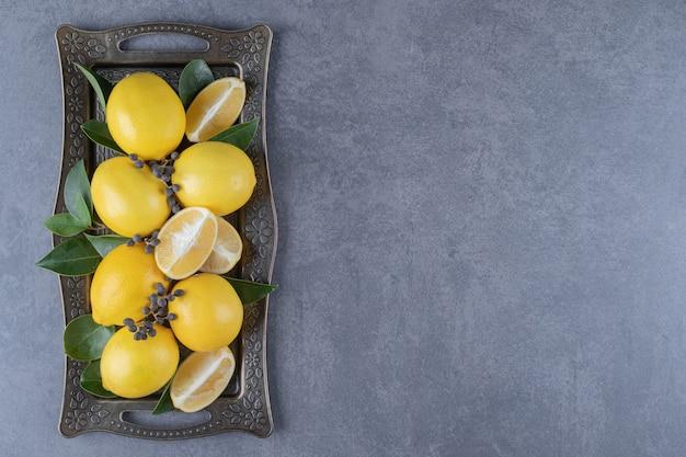 Fresh organic lemon and slices on board.