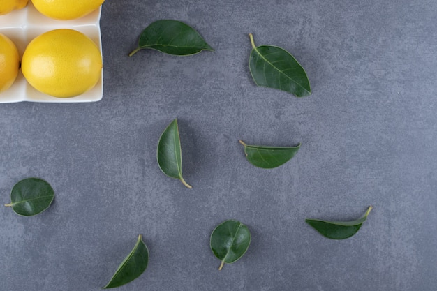 Fresh organic lemons and leaves over grey background.