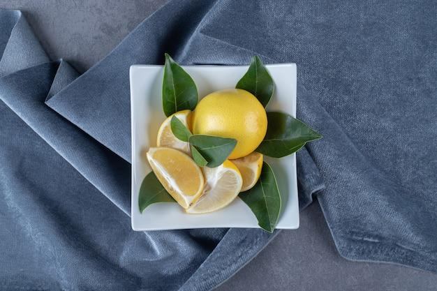 Fresh organic lemons and slices on white plate
